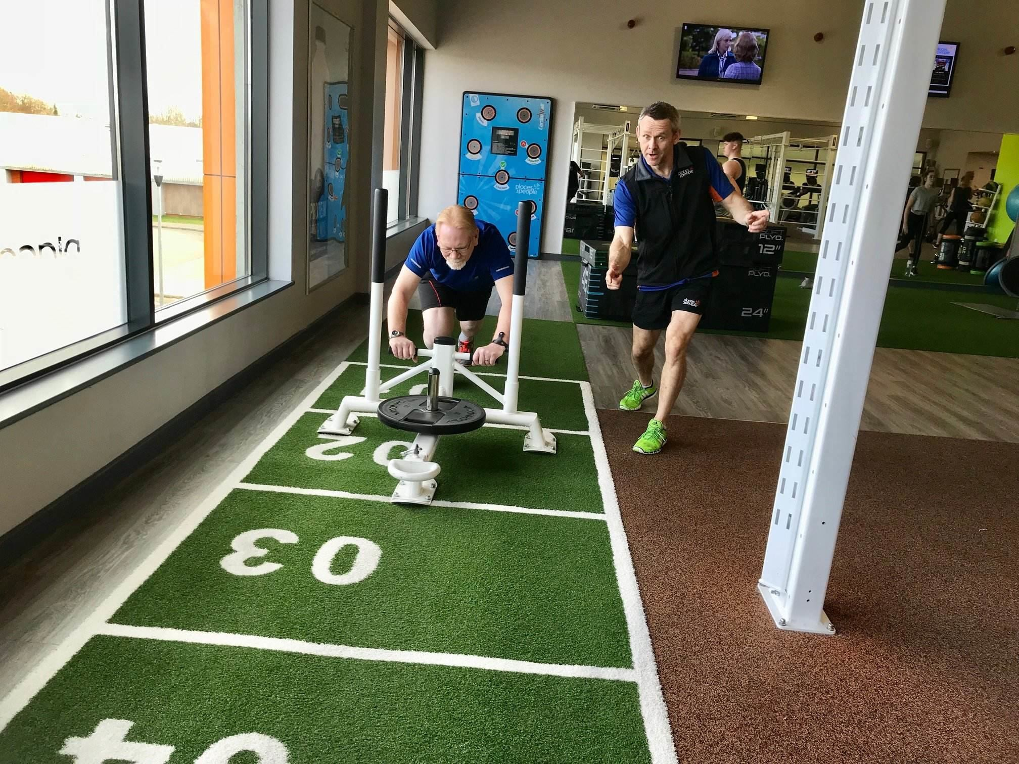 paul pushing sled in gym with steve